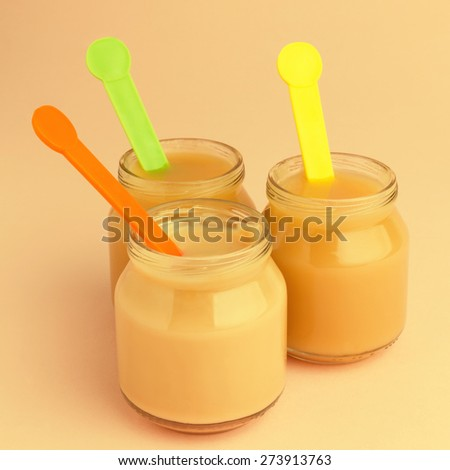 Close-up of jars of baby food with colorful spoons - stock photo