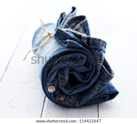 Close up of jeans roll over wooden surface - stock photo