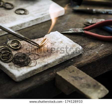 Close up of Jeweler crafting golden rings with flame torch. - stock photo