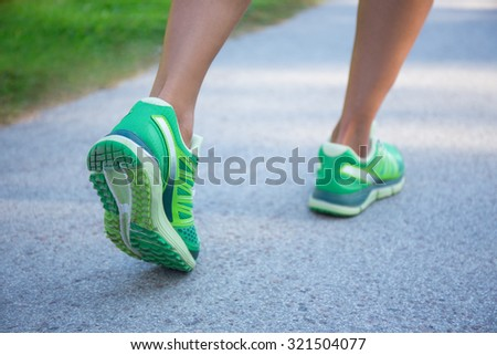 close up of jogging woman in green running shoes - stock photo