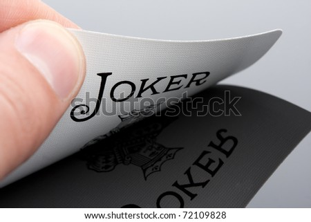 Close-up of Joker card in palm of hand - stock photo