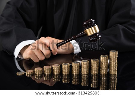 Close-up Of Judge Hands Hitting Gavel In Front Of Stacked Coins At Desk - stock photo