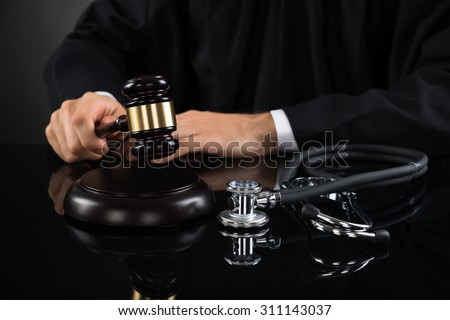 Close-up Of Judge Hands Hitting Gavel With Stethoscope In Courtroom - stock photo