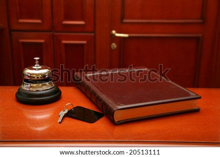 Close up of key, book and bell on wooden reception desk. Selection focus, focus on the bell. - stock photo