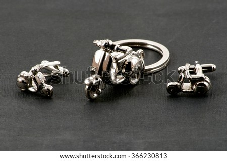 Close up of keychain motorbike and cufflinks over black - stock photo