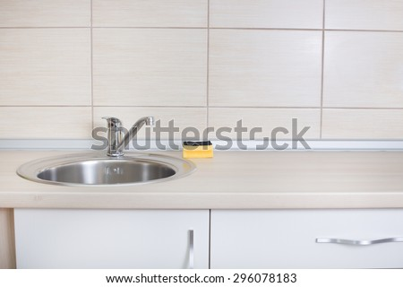 Close up of kitchen countertop with sink and sponge for dish cleaning - stock photo