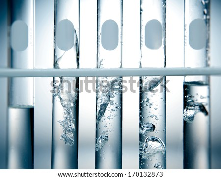 Close up of 5 laboratory test tube beakers with bubbling solution - stock photo