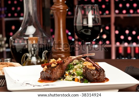 Close up of lamb chops with couscous and vegetables with a sauce of caramel, pepper and spices in a restaurant setting. - stock photo