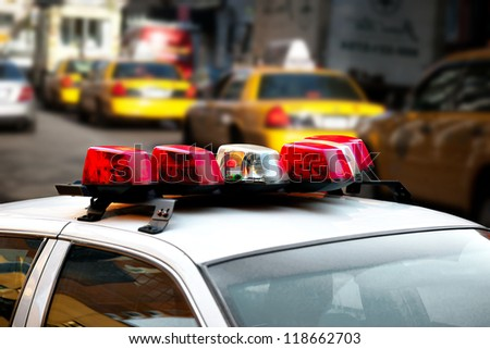 Close up of lamps on roof of New York police ca, with yellow cabs in background - stock photo