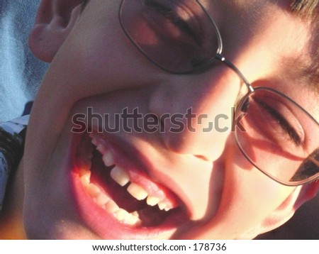 Close up of laughing boy in glasses - stock photo