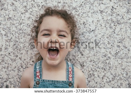 Close-up of laughing little girl against of granite wall - stock photo