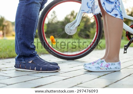 Close up of legs of boyfriend and girlfriend standing opposite each other. The bicycle is situated near them - stock photo