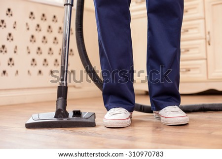 Close up of legs of male cleaner standing and vacuuming floor in a house - stock photo