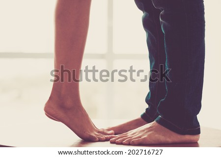 Close-up of legs of the kissing couple - stock photo