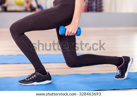 Close up of legs of young woman kneeling and doing exercise in gym. She is holding dumbbell - stock photo