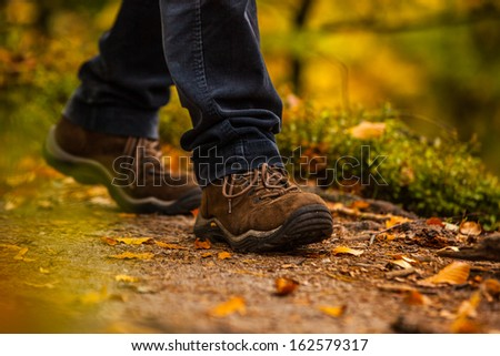 Close up of legs walking in narrow walkway in forest - stock photo