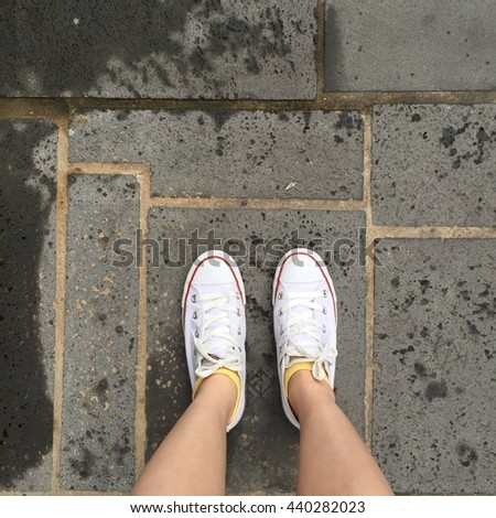 Close up of legs woman with leg and white sneakers outdoor great for any use. - stock photo