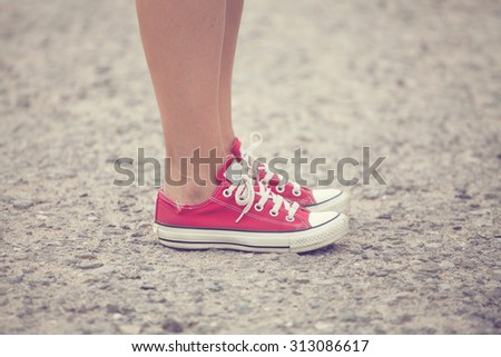 close up of legs woman with sneakers outdoor. soft vintage toned  - stock photo