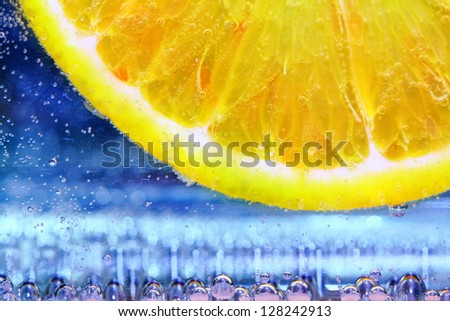 close up of lemon slice under water with bubbles on blue background - stock photo