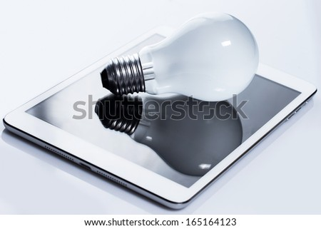 Close up of light bulb and white tablet pc - stock photo