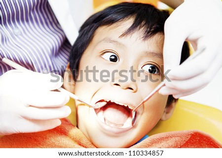 Close-up of little boy opening his mouth wide during inspection of oral cavity by dentist - stock photo