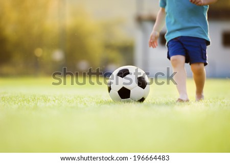 Close-up of little boy playing football on football pitch - stock photo