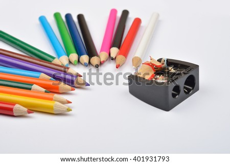 Close up of little colored pencils with black pencil sharpener and pencils shavings on it on white background. Selective focus - stock photo