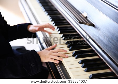 Close up of little girl hands piano playing - stock photo