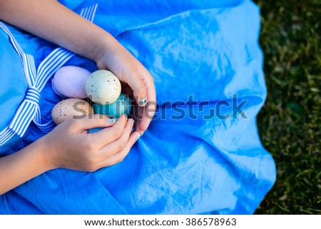 Close up of little girl holding colorful Easter eggs in her hands - stock photo