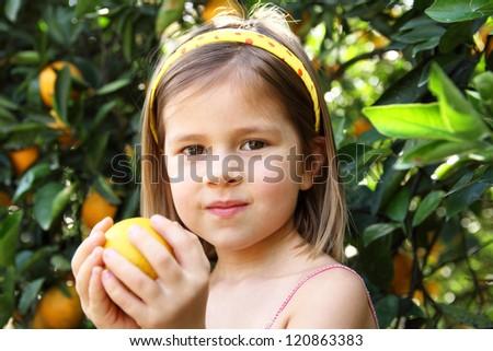 Close up of little girl holding orange - stock photo
