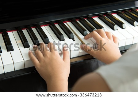 Close up of little girl playing music on piano - stock photo