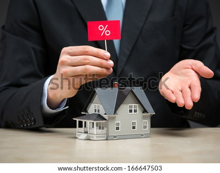 Close up of little home and hand keeping percent tablet. Concept of deal and real estate - stock photo