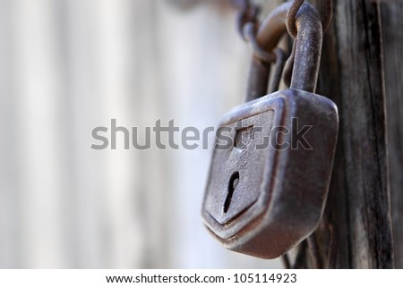Close-up of lock and chains on old door - stock photo
