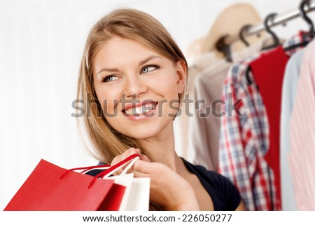 Close-up of lovely blond female shopaholic with colorful bags. Young pretty smiling woman buying clothes in shopping mall.  - stock photo