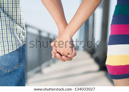 Close-up of lovers'?? hands holding each other - stock photo