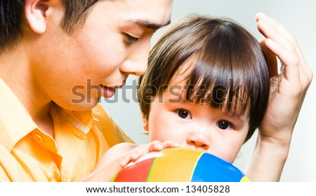 Close-up of loving father touching gently his little daughter's hair while she looking at camera - stock photo