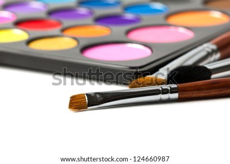 Close-up of make-up brushes with colorful eyeshadow palette. Isolated on white background - stock photo