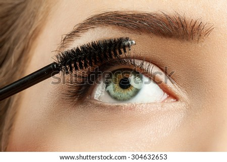Close-up of make-up green eye with long lashes with black mascara - stock photo