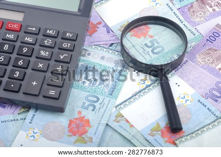 Close Up of Malaysia Bank Notes With Magnifying Glass and Calculator, Finance Concept Selective Focus - stock photo