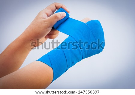 Close-up of male bandaging his arm - stock photo