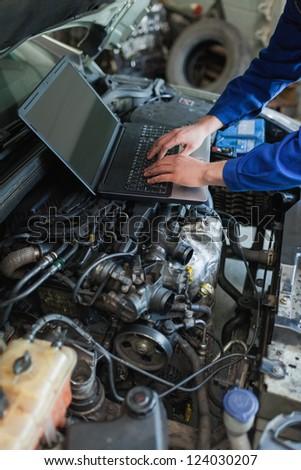Close-up of male car mechanic using laptop on car engine - stock photo