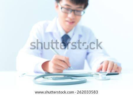 Close-up Of Male Doctor Filling The Medical Form - stock photo