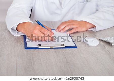 Close-up Of Male Doctor's Hand Filling Forms - stock photo