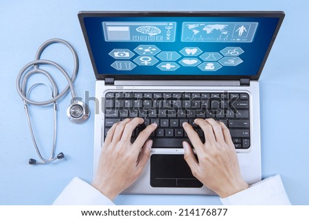 Close up of male doctor working on a laptop  - stock photo