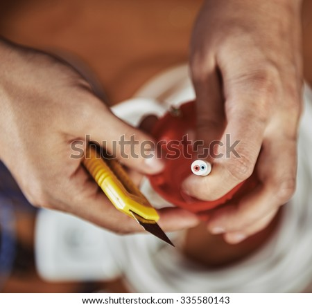 Close-up of male electrician's hands cutting electrical cable with construction knife. Man technician repairing socket in a room. - stock photo
