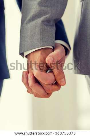 close up of male gay couple holding hands - stock photo