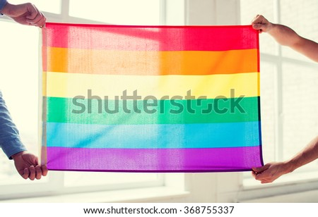 close up of male gay couple holding rainbow flag - stock photo