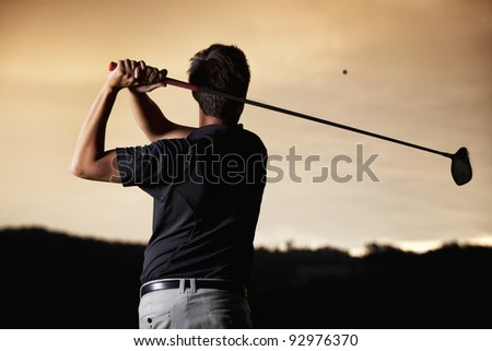 Close up of male golf player in black shirt teeing-off ball in twilight, view from behind. - stock photo