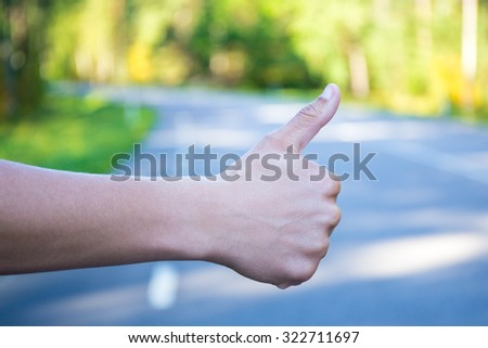 close up of male hand hitchhiking on forest road - stock photo