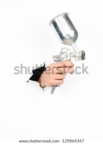 close-up of male hand holding a silver spray gun through a torn white paper, isolated - stock photo